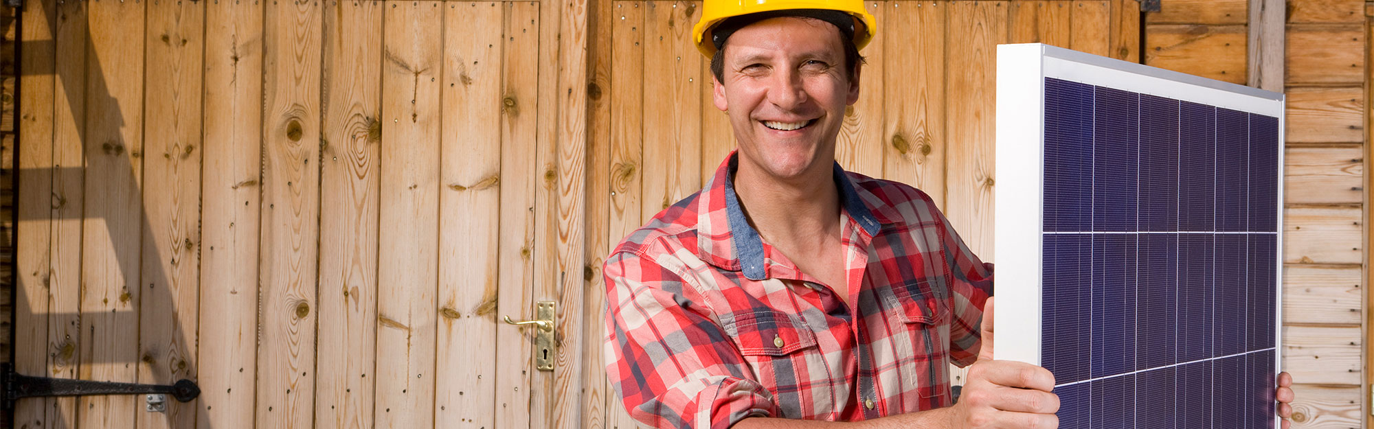 Smiling man holding solar panel in front of cabin.