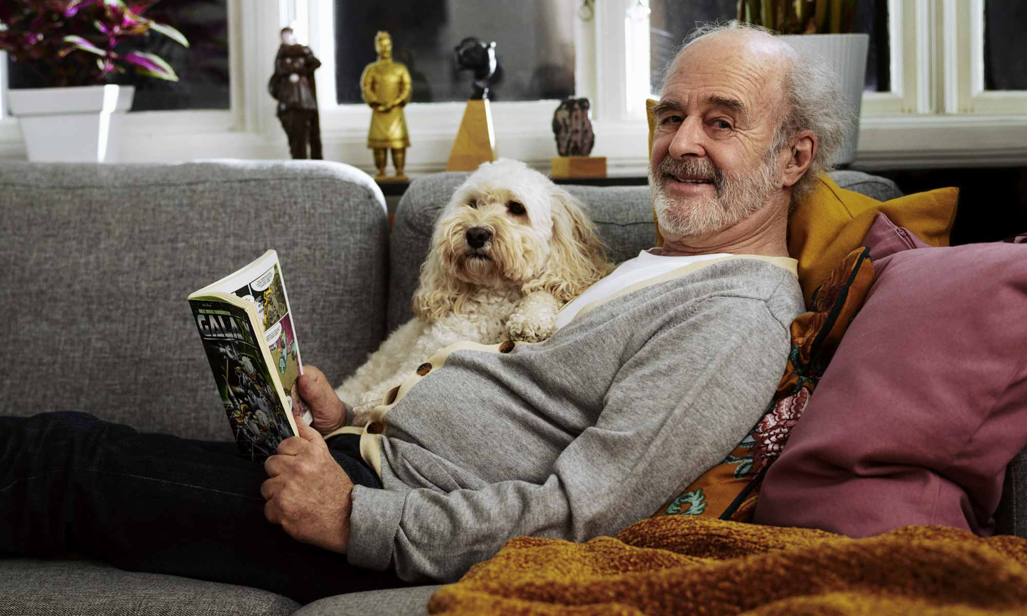Senior man on the couch with a dog